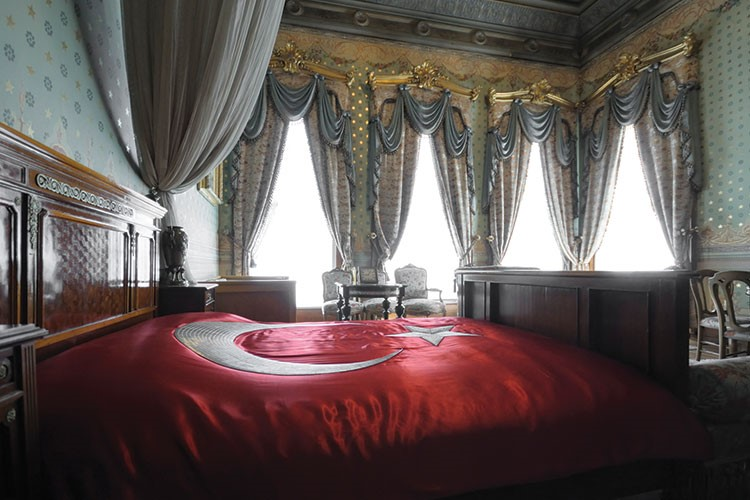 a bed with a red bed spread