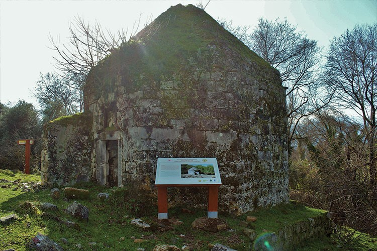 a stone building with a sign in front of it
