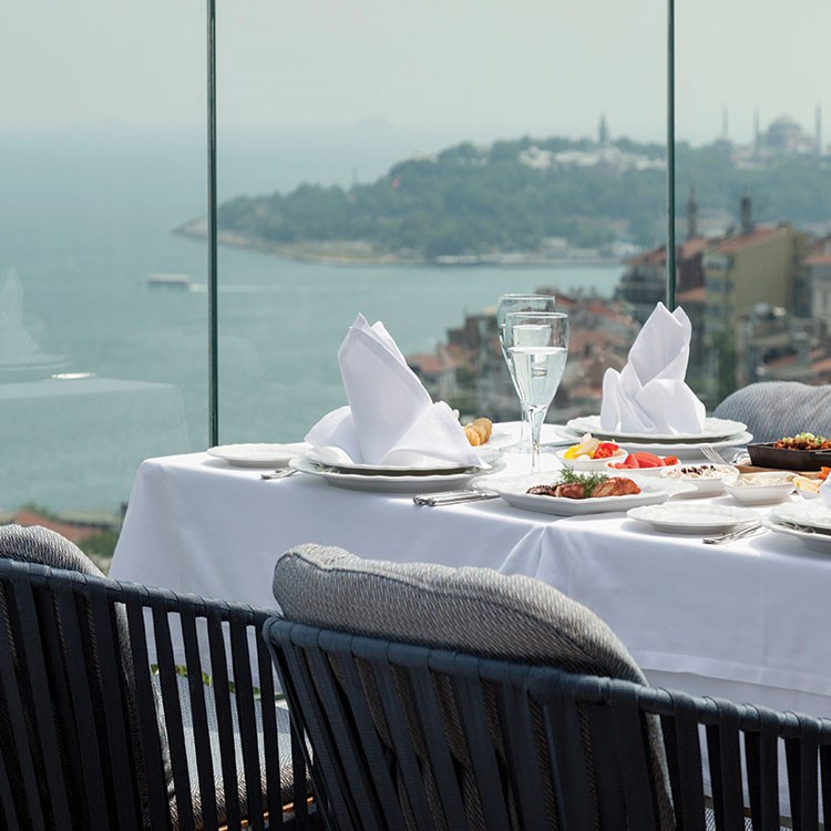 a table with plates and glasses on it by a body of water
