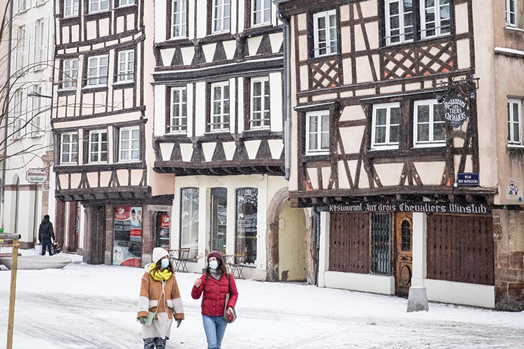 a couple of people walking in the snow next to a row of buildings