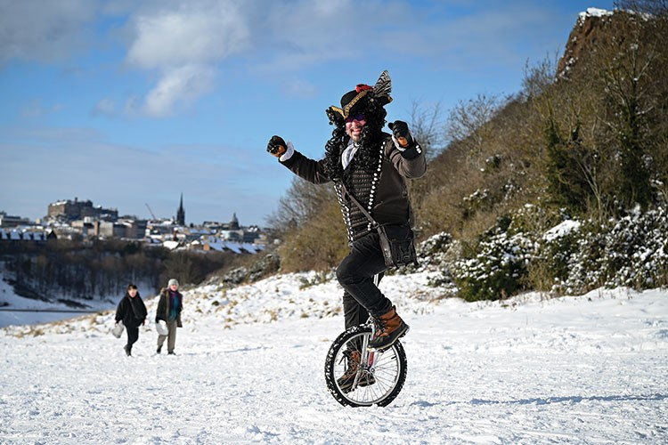 a man riding a bicycle on a snowy hill