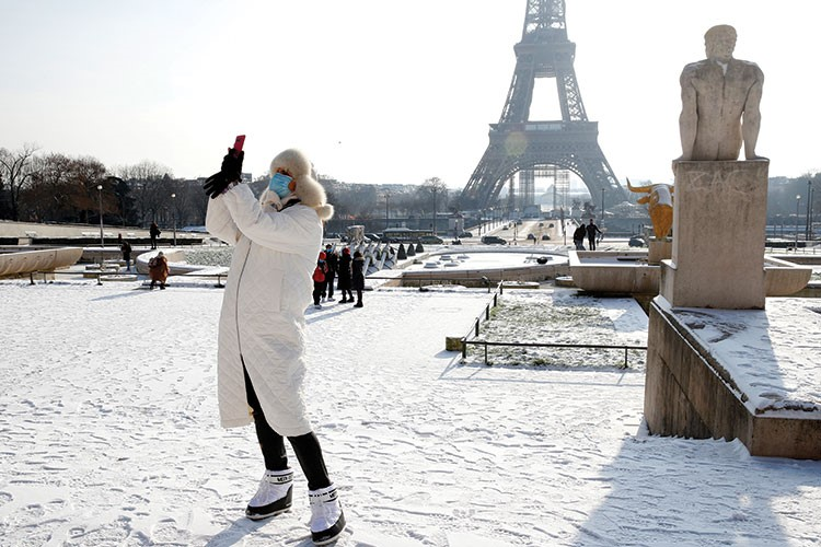 a person in a white coat and mask in a snowy place