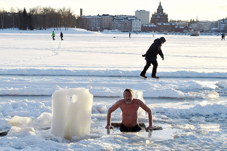 a person sitting on ice with people in the background