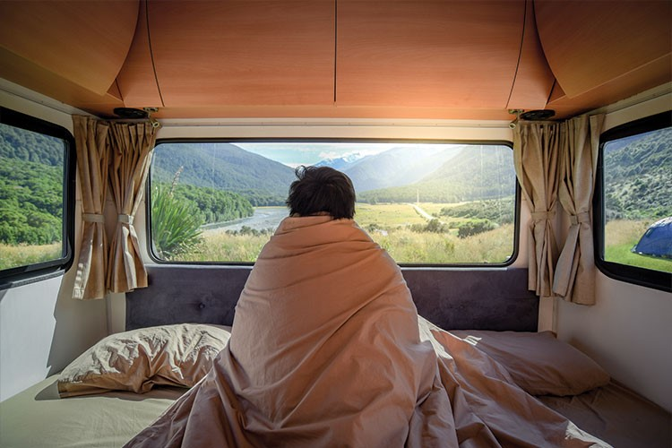 a person sitting on a bed looking out a window