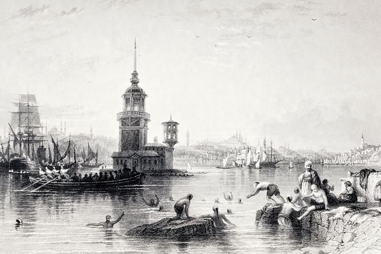 a group of people in a body of water with a building in the background