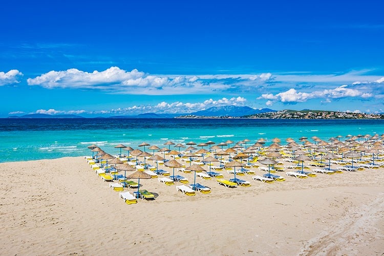 a beach with many umbrellas and chairs