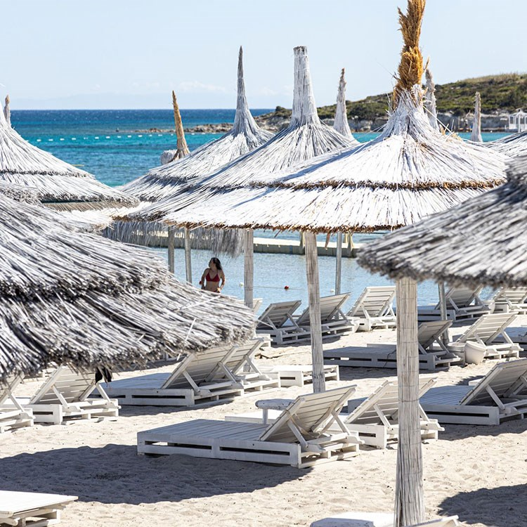 a beach with umbrellas and chairs