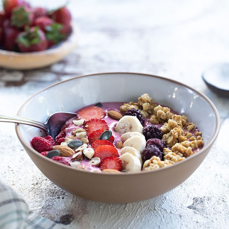 a bowl of cereal with milk and berries