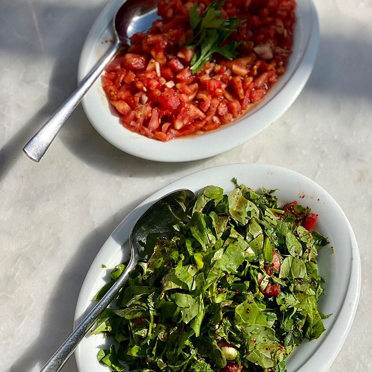a bowl of salad next to a bowl of broccoli and a bowl of salad