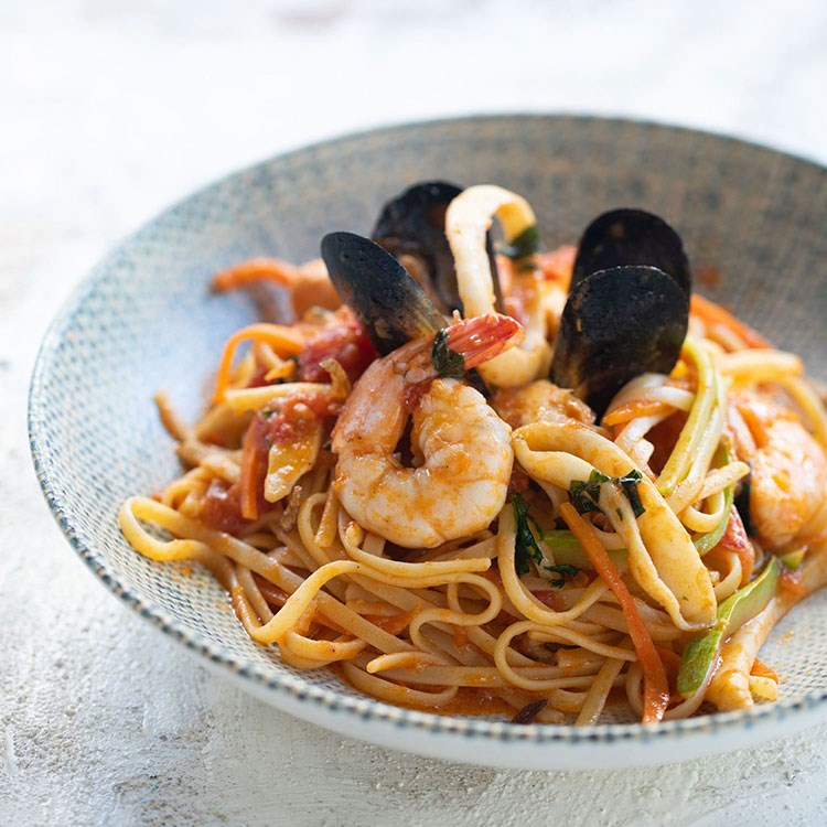 a bowl of spaghetti with shrimp and vegetables
