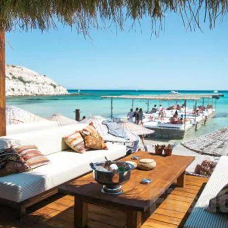 a lounge area with a table and chairs and a beach with people