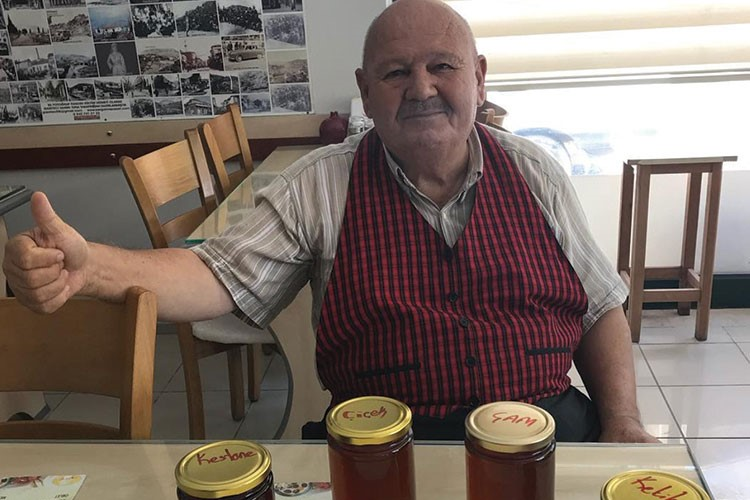 a man sitting at a table with a group of jars of food