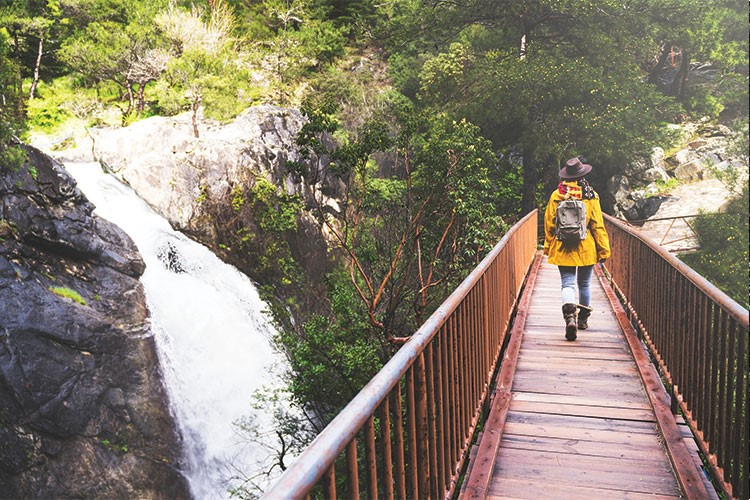 a person walking on Kempty Falls over a river