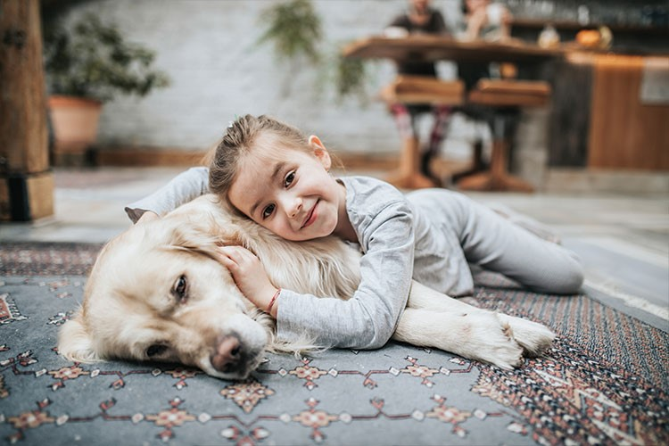 a girl lying on the ground with a dog