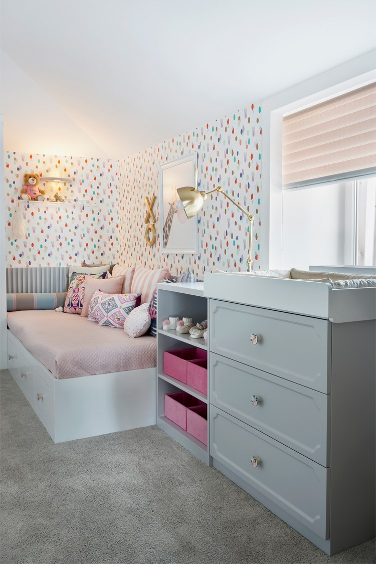 a bedroom with a pink and white wallpaper