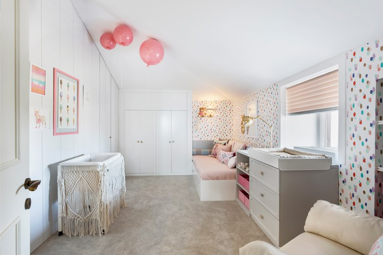 a room with a bed and a basket with balloons