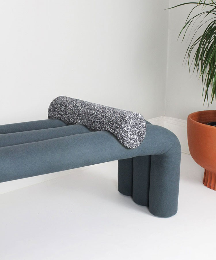 a grey couch with a grey pillow