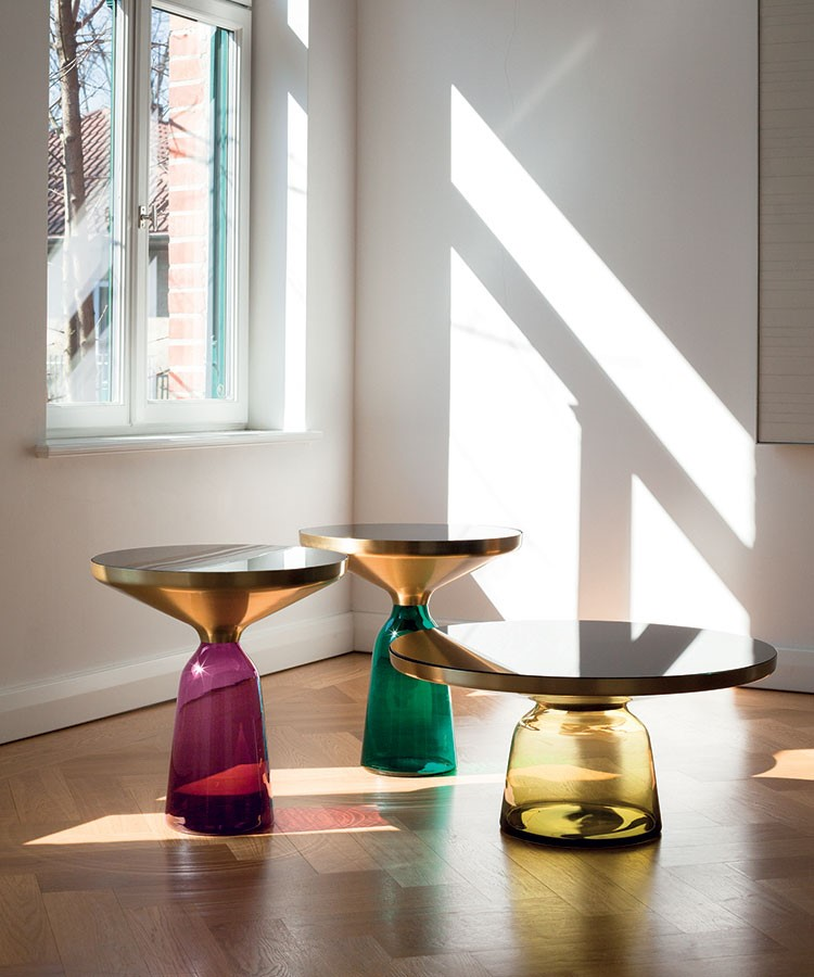 a group of colorful vases sit on a table