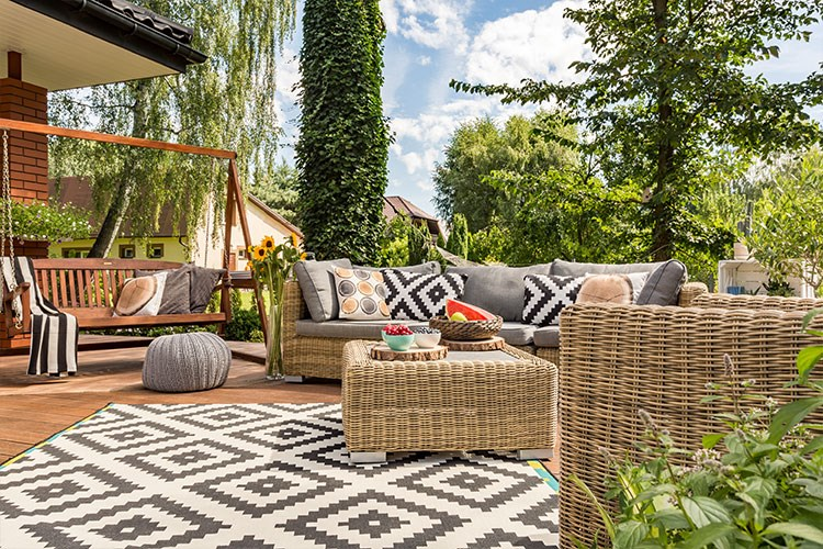a patio with a couch and a table with a basket and a basket