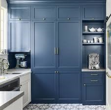 a blue kitchen with white cabinets