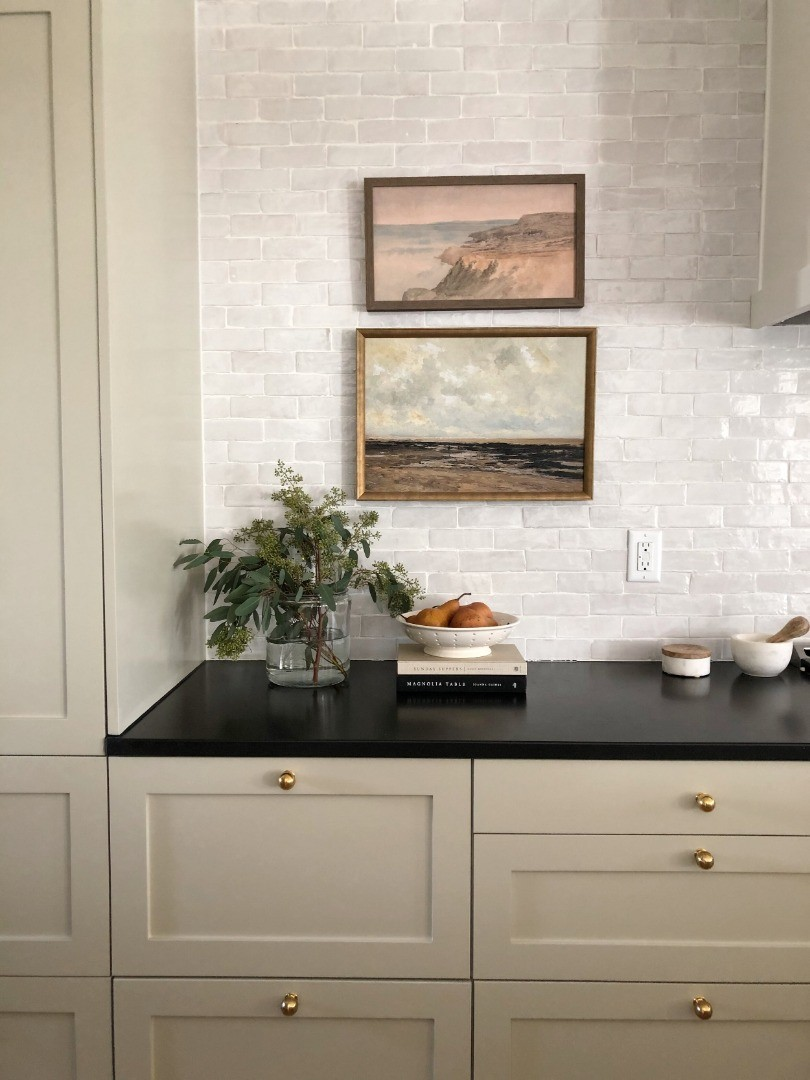 a kitchen with a black countertop and white cabinets