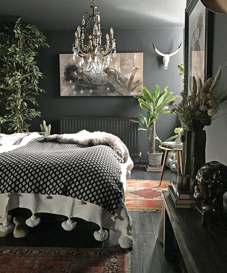 a bedroom with a bed and a chandelier