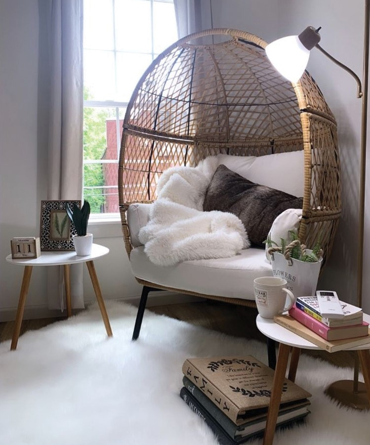 a chair with a table and a lamp in a room with a window