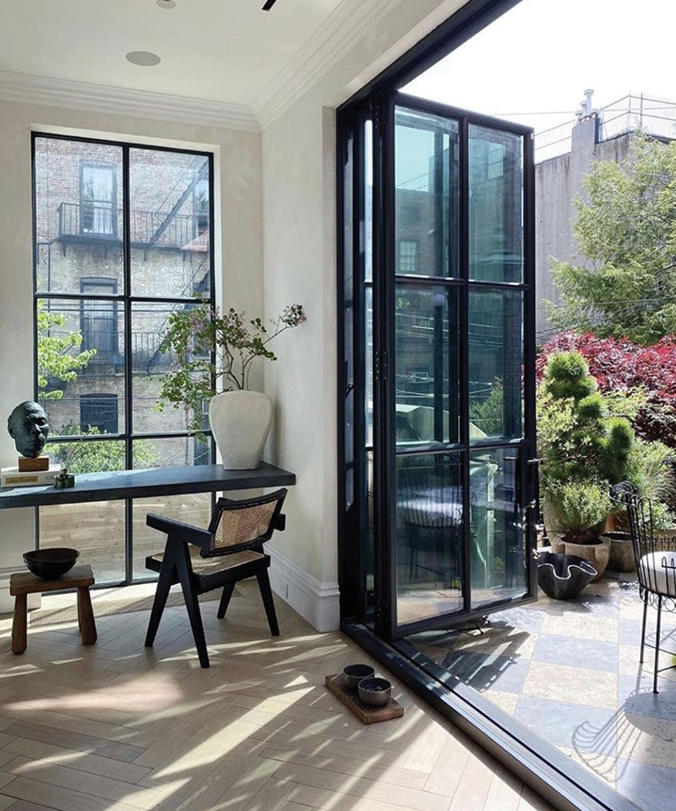 a room with a glass door and a table with chairs and plants