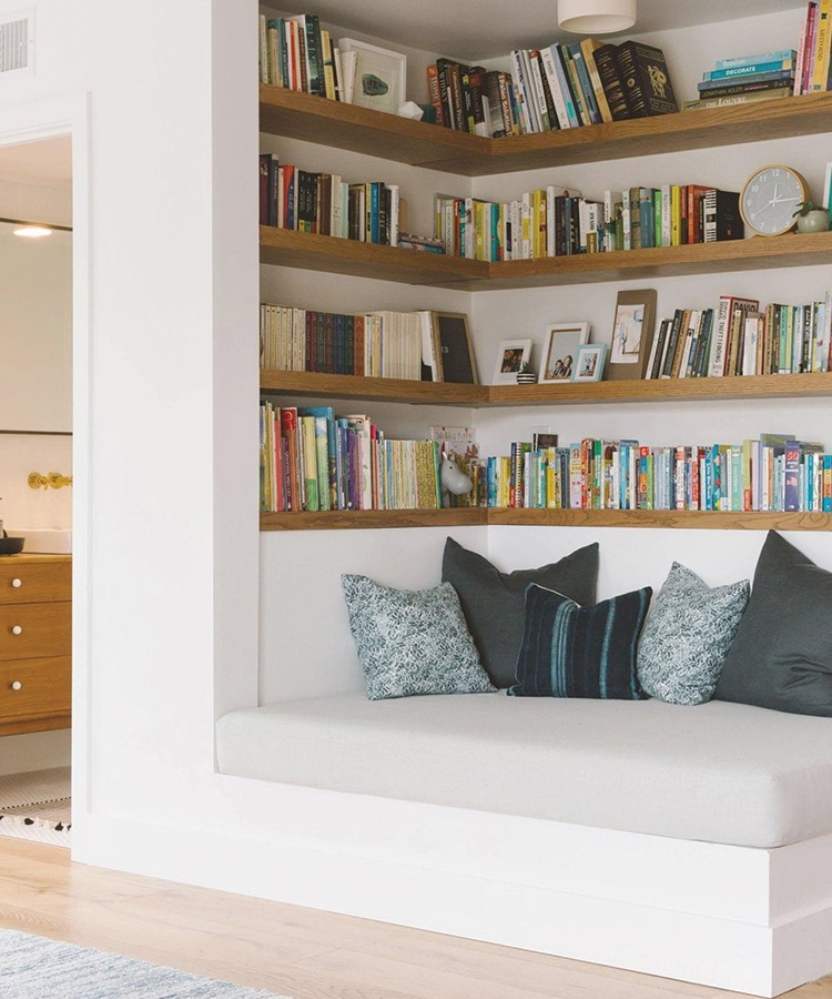 a white couch in front of a book shelf