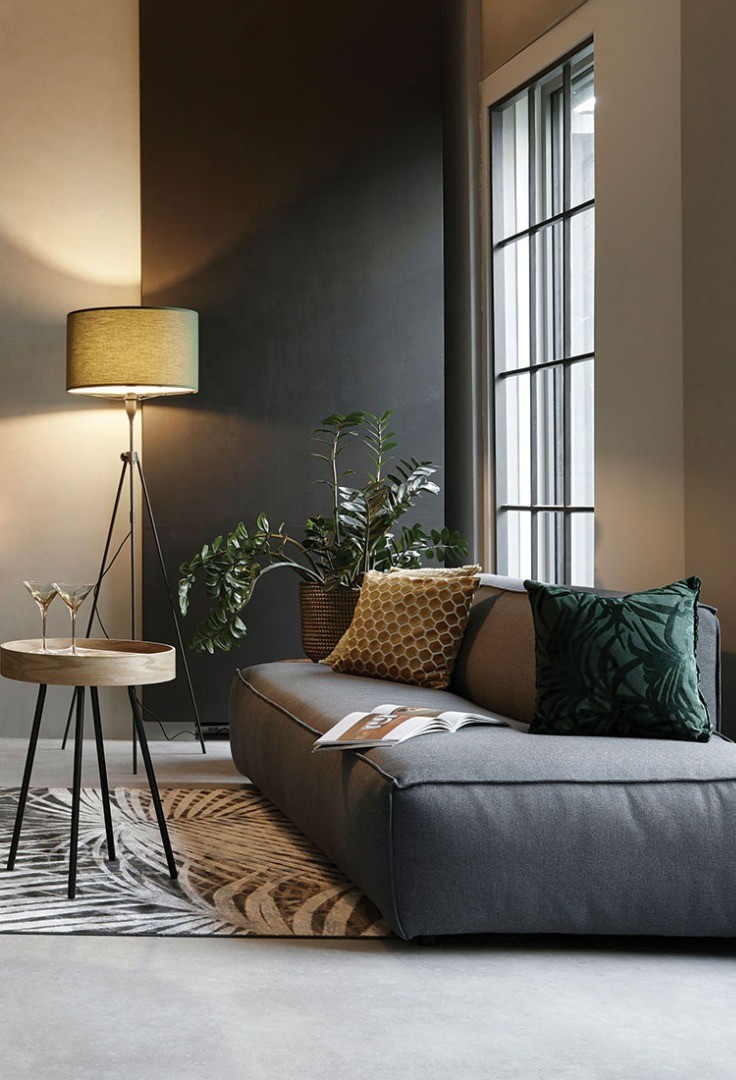 a couch with pillows and a lamp