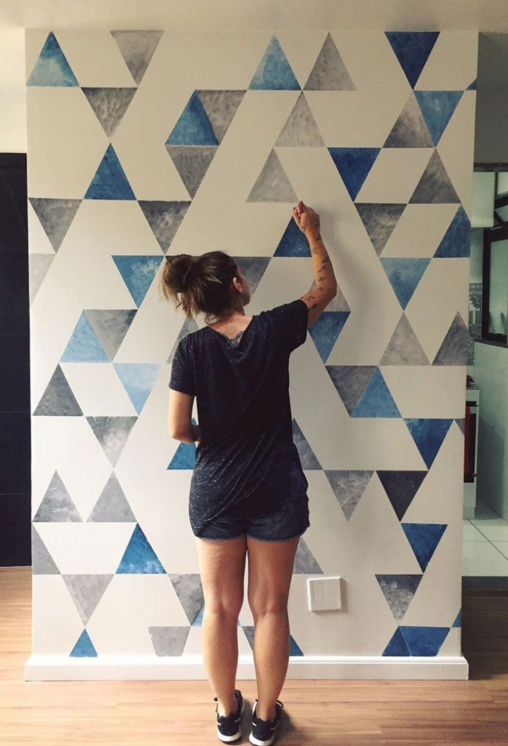 a person standing in front of a wall with a design on it