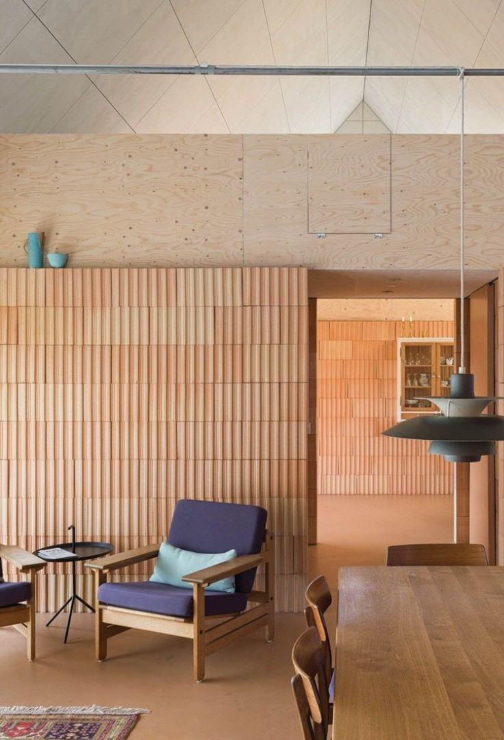 a room with a table chairs and a wall with a tile wall