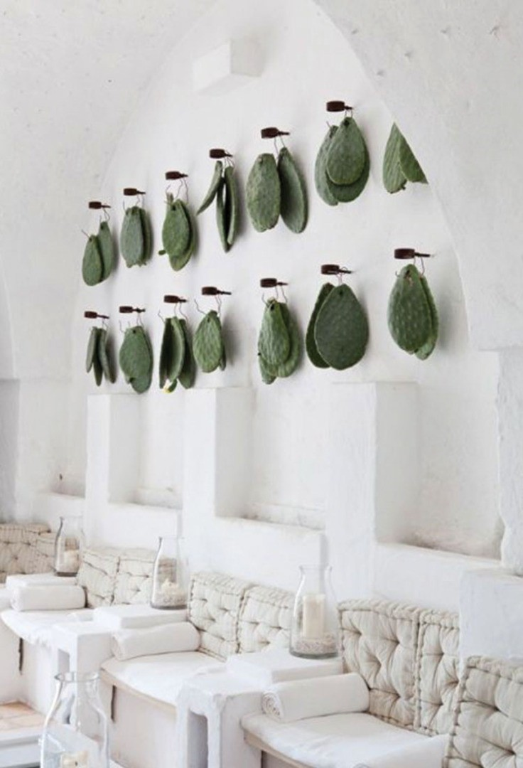 a room with a wall of glass vases and bottles