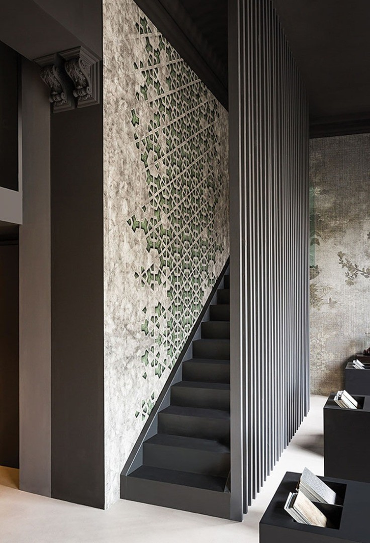 a staircase with a wall of green plants
