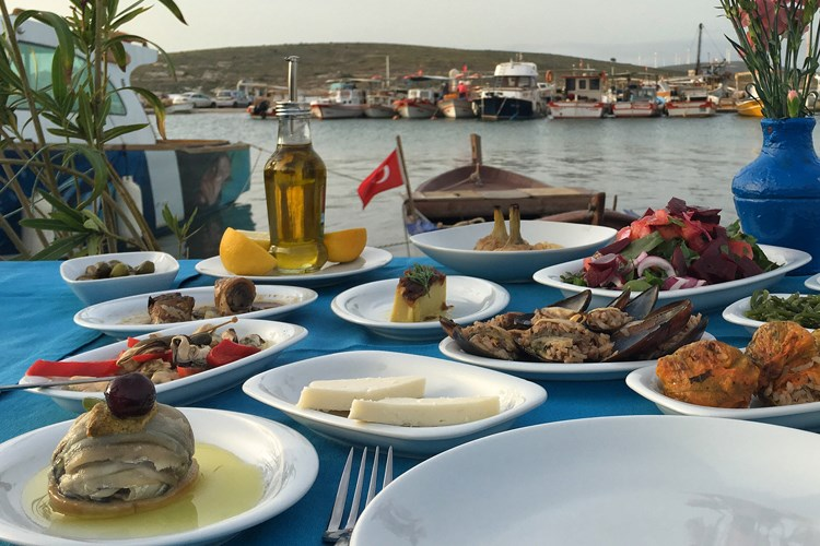 a table with plates of food and a body of water in the background