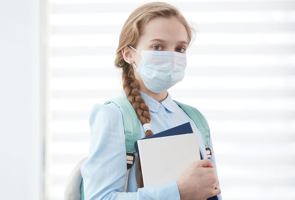 a person wearing a mask and holding a clipboard