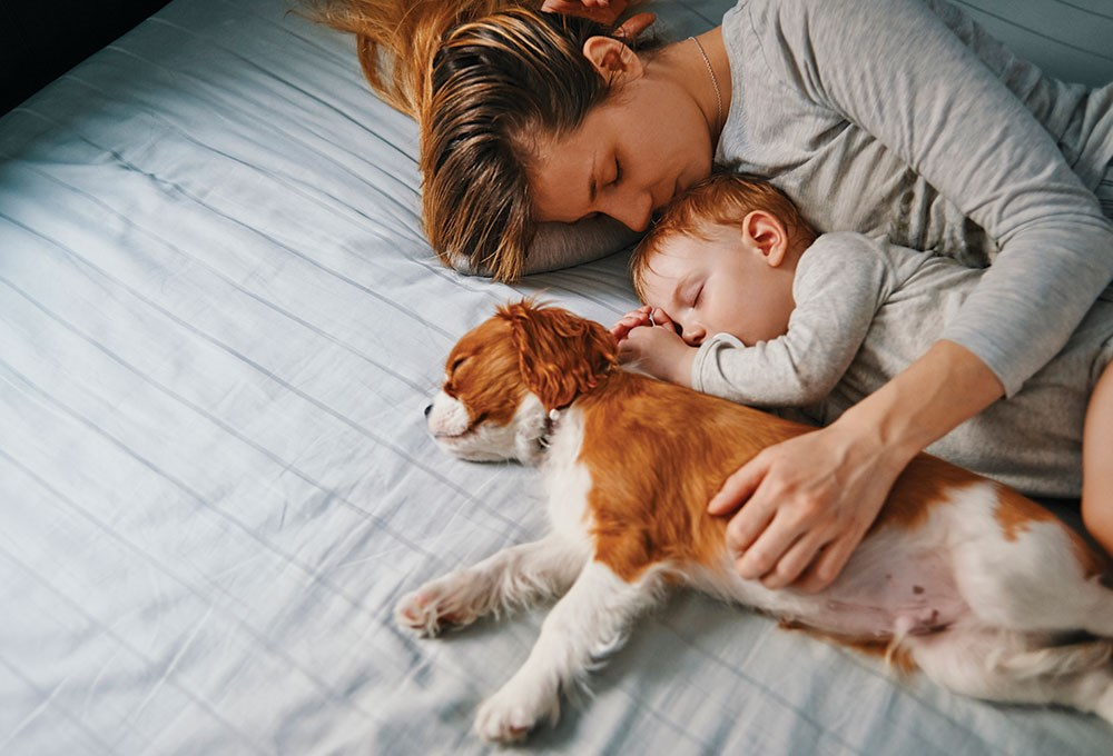 a person and a baby sleeping on a bed