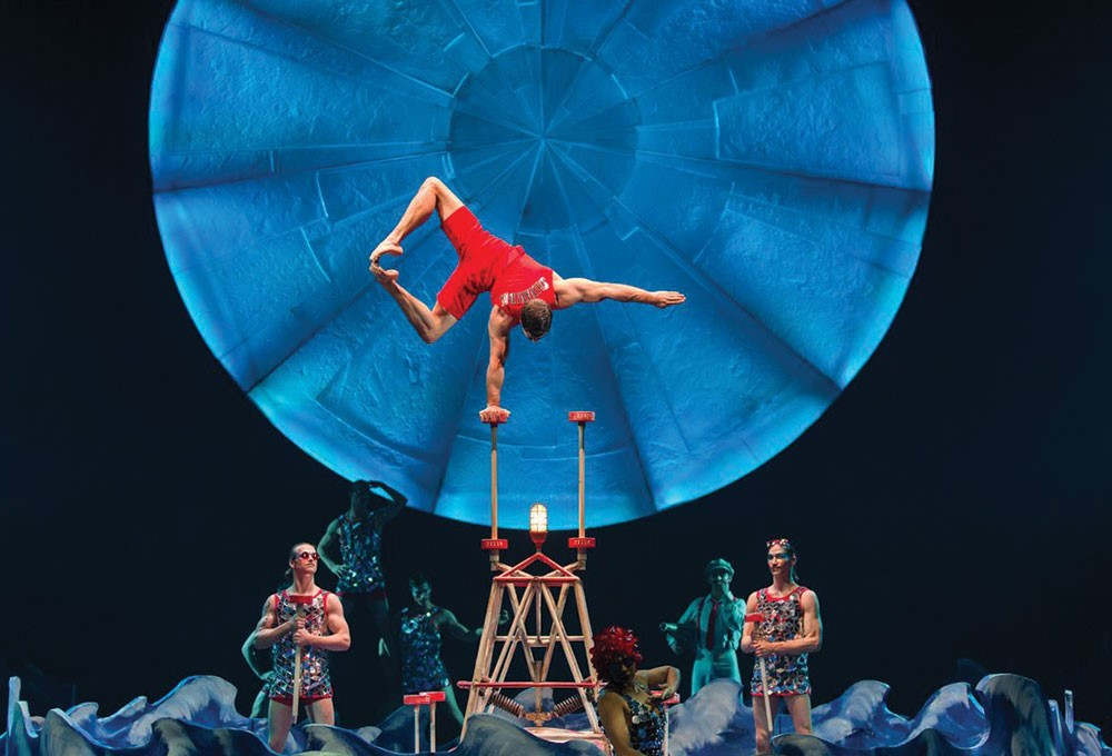 a person in a red shirt and shorts in mid air above a group of people in clothing