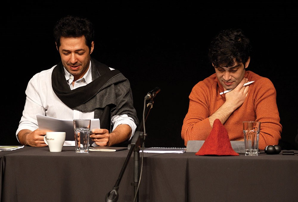 Mert Firat et al. sitting at a table with microphones and cups