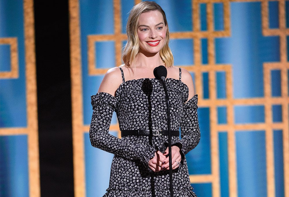 Margot Robbie standing in front of a microphone