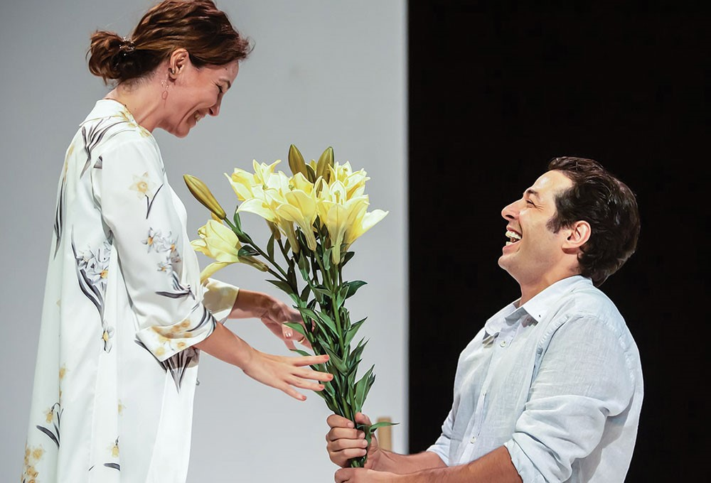 a woman holding a yellow flower next to a man