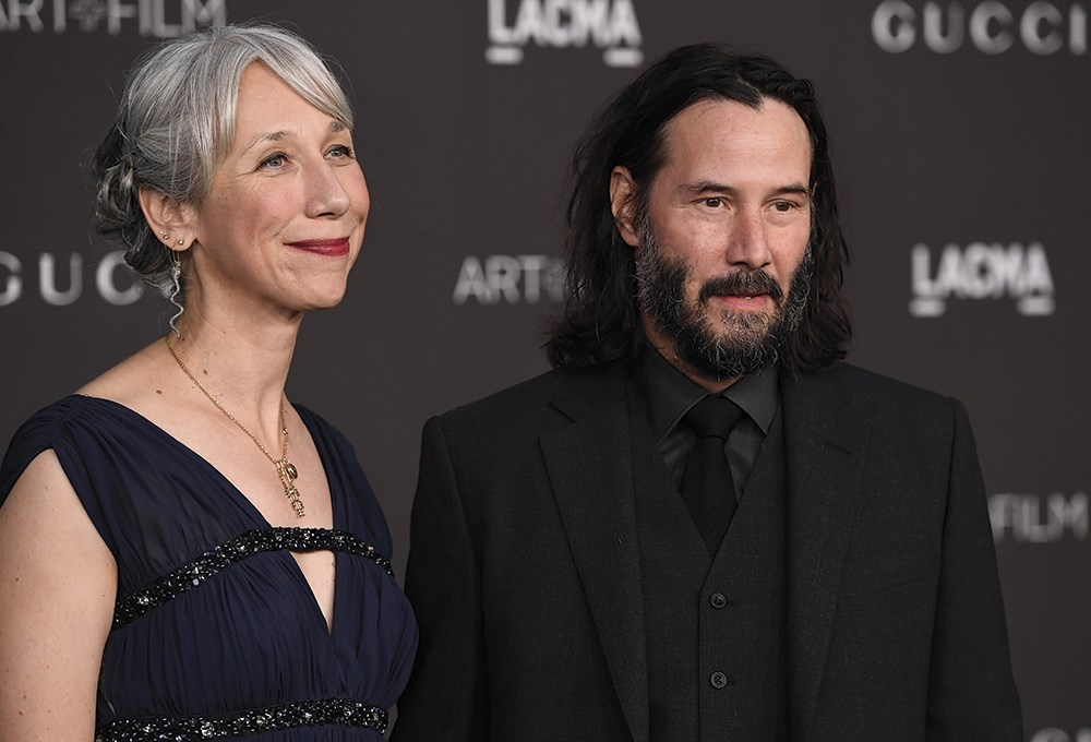 Keanu Reeves, Alexandra Grant are posing for a picture