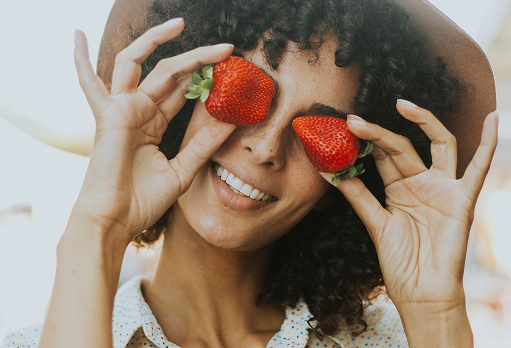 a woman holding a strawberry