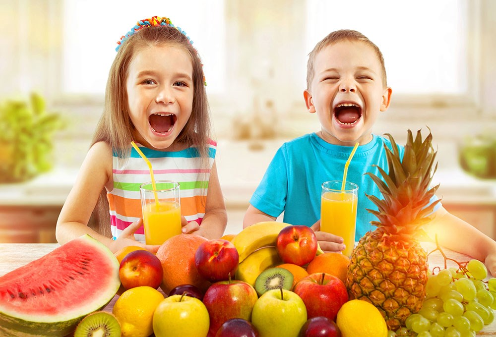 a couple of kids with fruit