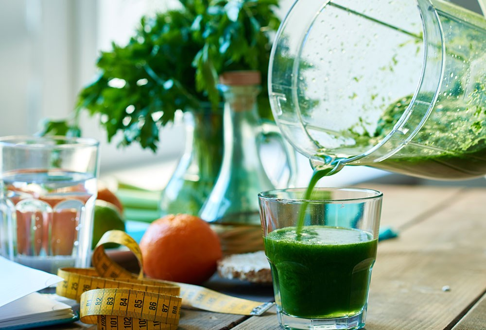 a glass of green liquid next to a glass with a plant in it