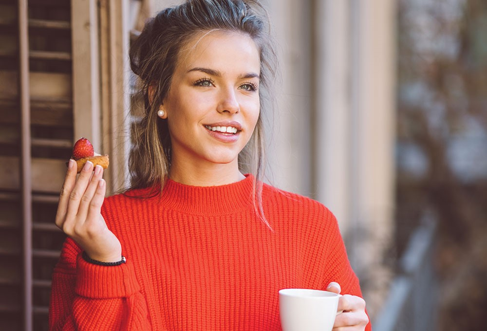 a person holding a cup and a strawberry