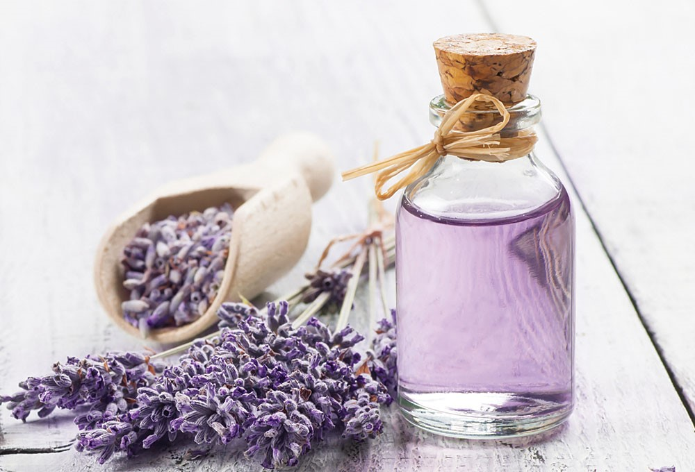 a bottle of perfume next to a bowl of purple flowers
