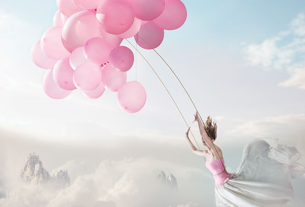 a person holding a bunch of balloons