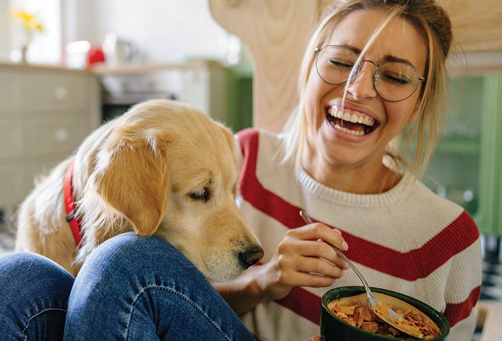 a woman eating a bowl of food with a dog