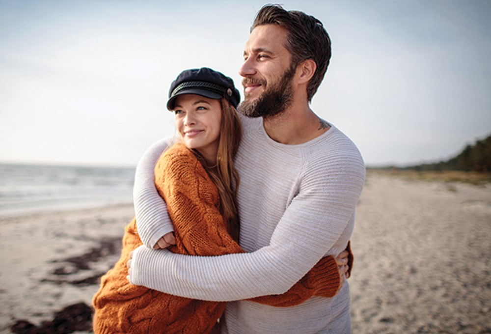 a man and woman hugging on a beach